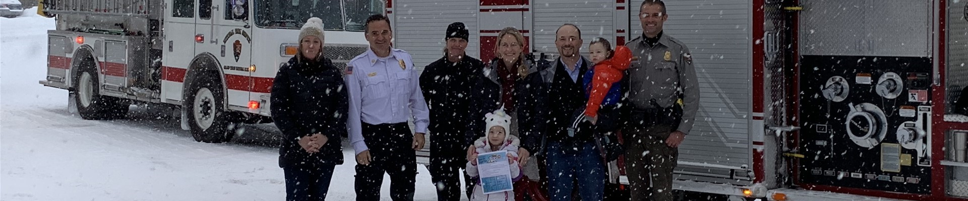 Kelly Elementary student Isabell Dragoo with her parents, principal and members of Jackson Hole Fire/EMS and Grand Teton National Park